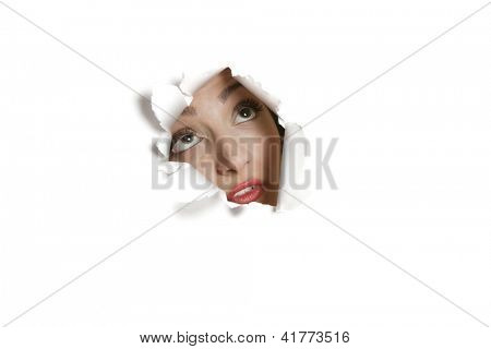 Young Middle eastern woman looking up from ripped paper hole