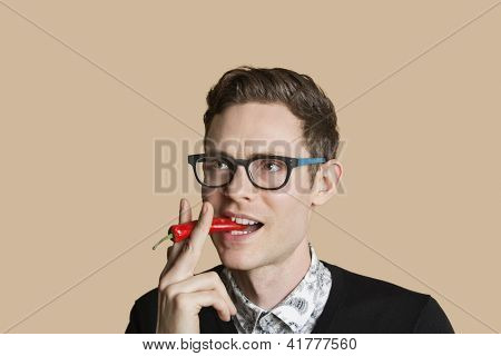 Young man smoking red chili pepper over colored background