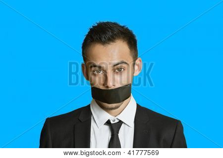 Portrait of a young businessman with adhesive tape on mouth over colored background