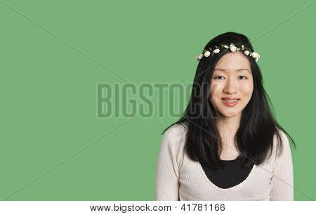 Portrait of a cute young woman wearing a hair wreath over green background