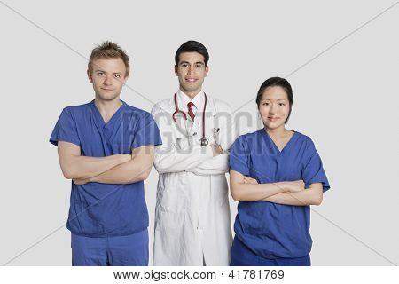 Retrato de diversos profissionais de saúde, de pé com as mãos dobradas sobre fundo cinza