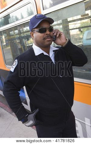 African American bus driver answering phone call while standing by a bus