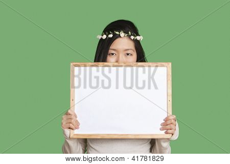 Portrait of a young woman hiding her face with a blank whiteboard over green background