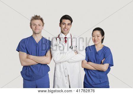 Retrato de multi étnica profissionais de saúde em pé com os braços cruzados sobre fundo cinza