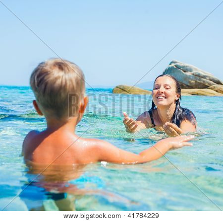 Mother with her son swimming in sea