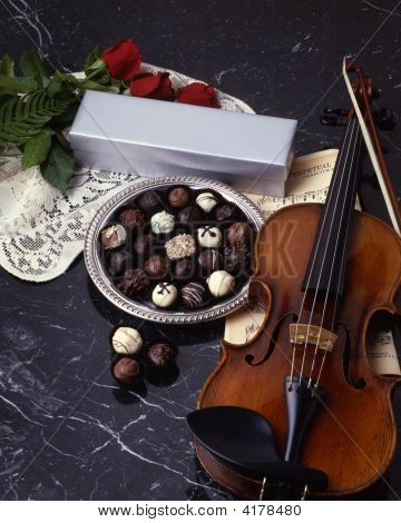 Chocolate Truffles And Violin On Black Marble