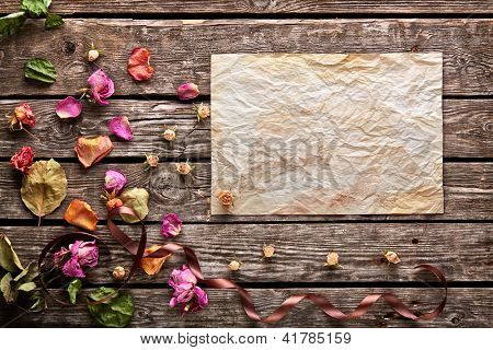 Abstract holiday background with blank sheet of old crumpled paper on vintage wooden plates. With rose petals, curved ribbon, dried flowers.