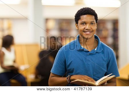 male african american college student reading book in library
