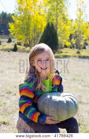 Kid little girl holding halloween pumpkin in outdoor nature smiling