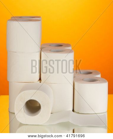 Rolls of toilet paper on orange background