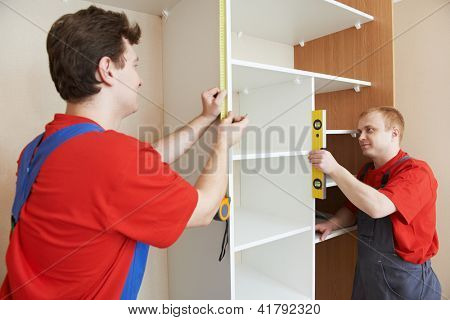 Two carpenters workers joint and settle home built-in cupboard