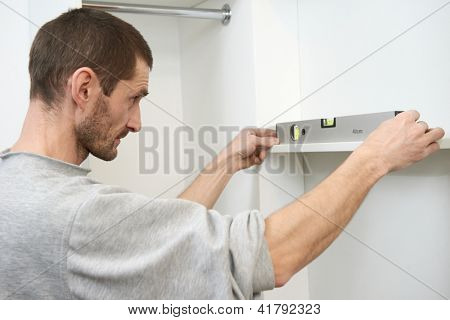 Joiner carpenter worker examining and control home built-in cupboard with level