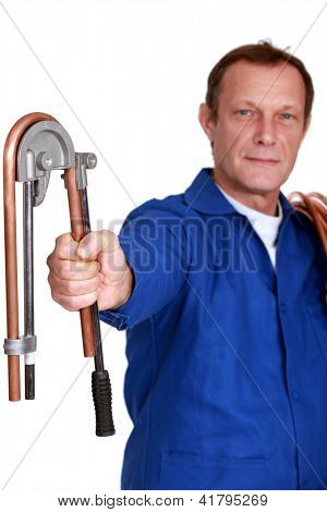 Plumber using tool to bend copper pipe
