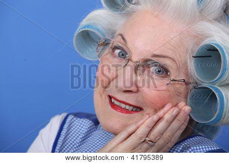 Elderly lady using hair rollers
