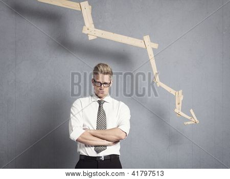 Concept: Business failure. Miffed irritated businessman in front of business graph pointing down, isolated on grey background.