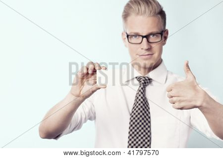 Young smiling businessman giving thumbs up at white blank business card with space for text while holding it, isolated.