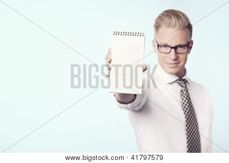 Friendly young businessman showing blank notepad with space for text, isolated.