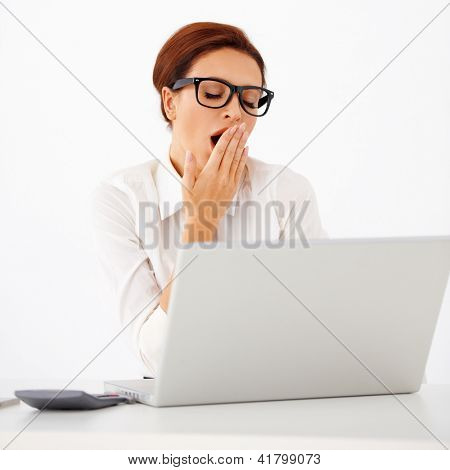 Attractive tired young businesswoman wearing glasses yawning with her hand to her mouth as she sits at her desk with a laptop