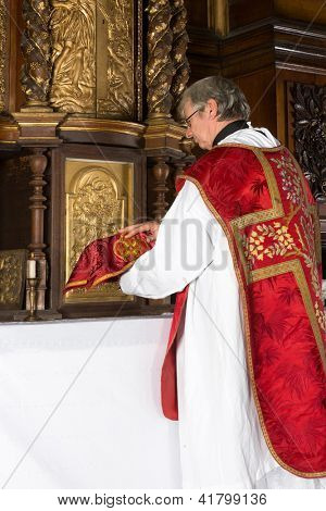 Catholic priest putting a covered chalice back into the tabernacle of a medieval church with 17th century interior