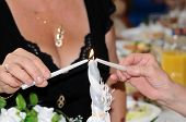 stock photo of unity candle  - Parents of bride and groom lighting a white unity candle at their wedding - JPG