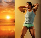 stock photo of glorious  - Sexy portrait of an active young fit male model in underwear and tank against wall near glorious sunrise in golden light - JPG