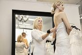 stock photo of half-dressed  - Senior owner assisting young bride getting dressed in wedding gown - JPG