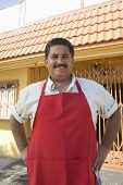 Portrait of hispanic male restaurant owner in red apron standing with hands on hips