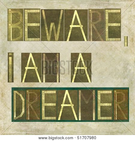 "Earthy textured background image and design element depicting the words ""Beware, I am a dreamer"""