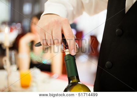 Waiter uncorking a wine bottle in a restaurant