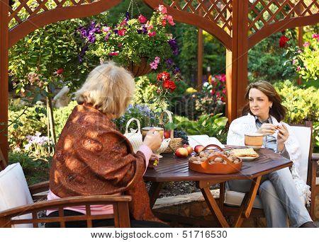 Women Drinking Coffee In A Garden Outdoors