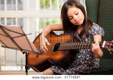 Cute little girl playing the guitar poster