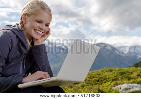 Young Blond Woman With A Laptop Before A Mountain Landscape