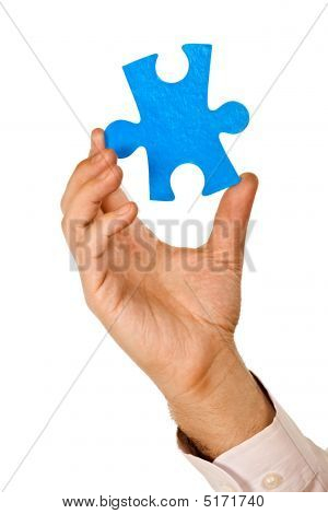 Businessman Holding A Piece Of Puzzle