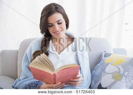 Peaceful casual brown haired woman in white pajamas reading a book in a bright living room