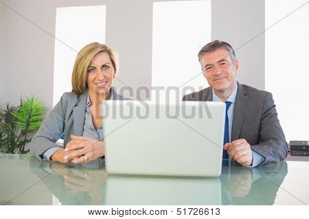 Two smiling mature business people looking at camera behind an opened laptop at office