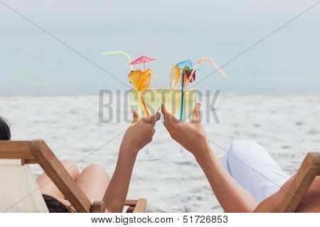 Couple clinking glasses of cocktail on beach in front of ocean
