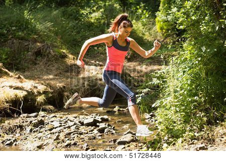 Sporty young woman leaping over a stream in a forest on a run