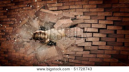 Human hand breaking brick wall. Strength and power