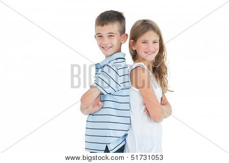 Happy young brother and sister posing back to back on white background
