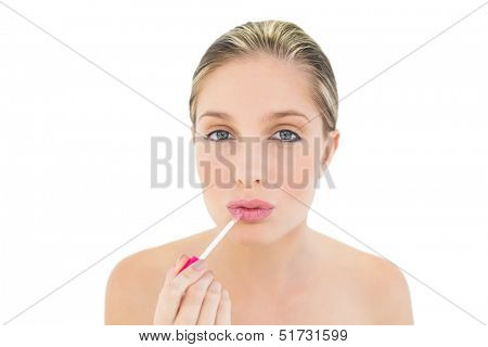 Pretty fresh blonde woman pouting and applying gloss on white background