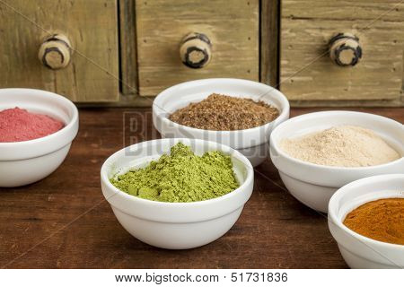 super fruit and leaf powders in small ceramic bowls - baobab, noni, yumberry, moringa, mangosteen