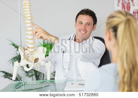 Smiling doctor showing a patient something on skeleton model in bright office