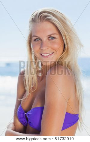 Attractive woman smiling at camera on beach on holidays
