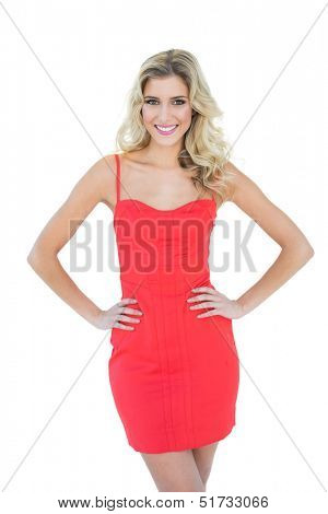 Cheery smiling blonde model posing with hands on hips on white background