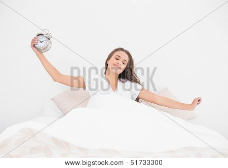 Peaceful smiling brunette holding alarm clock in bright bedroom