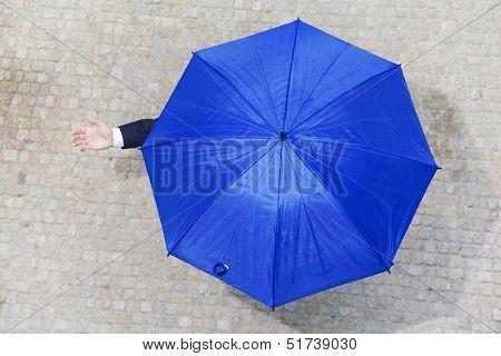 Confident businessman hidden under umbrella and checking if it's raining