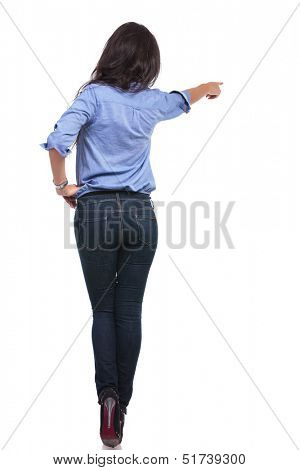 back view of a young casual woman pointing away from the camera with a hand on her hip. on white background