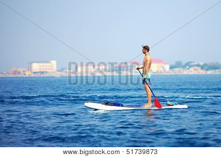 Young Man Standing On Paddle Board In The Sea