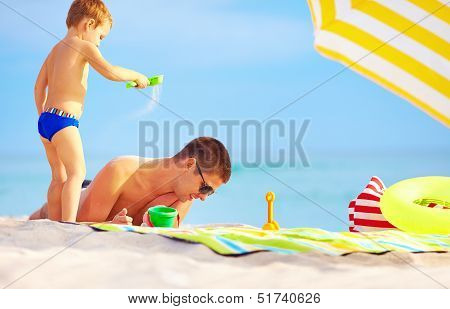 Playful Son Strews Sand On Father, Colorful Beach