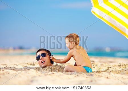 Happy Kid Helping Father In Sand Talk On The Mobile Phone